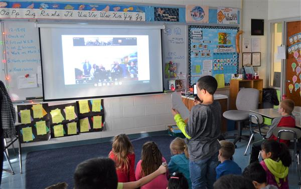 Photo of student asking question to students on video screen