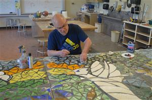 Photo of teacher grouting mosaic tiles