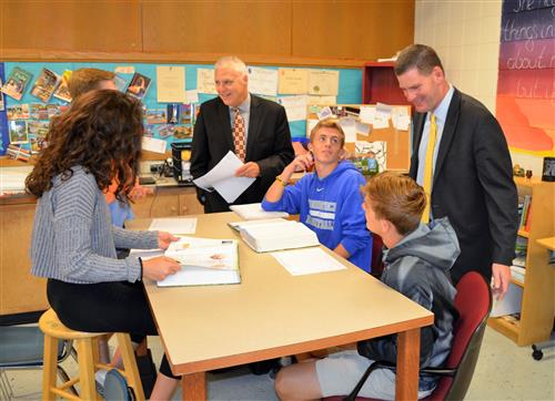 Photo of superintendent and college president talking to students