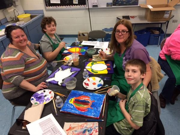 Families enjoying paint night with Mrs. Menge