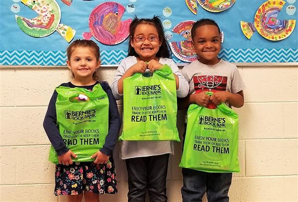 Photo of children holding bags of books
