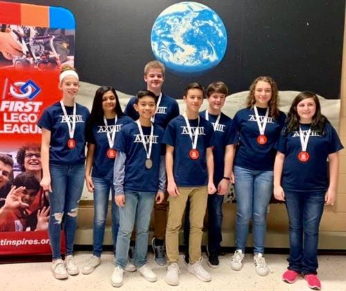 Photo of students posing with robotics medals