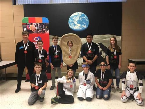Photo of students posing with robotics medal