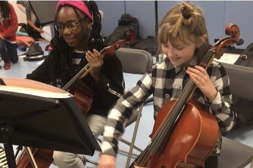 Two elementary students practicing cello