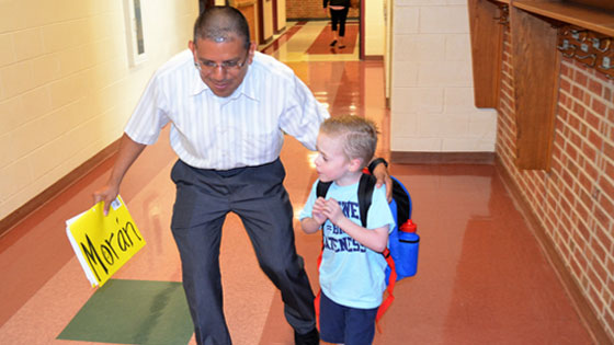 Teacher walking in hall with a young student