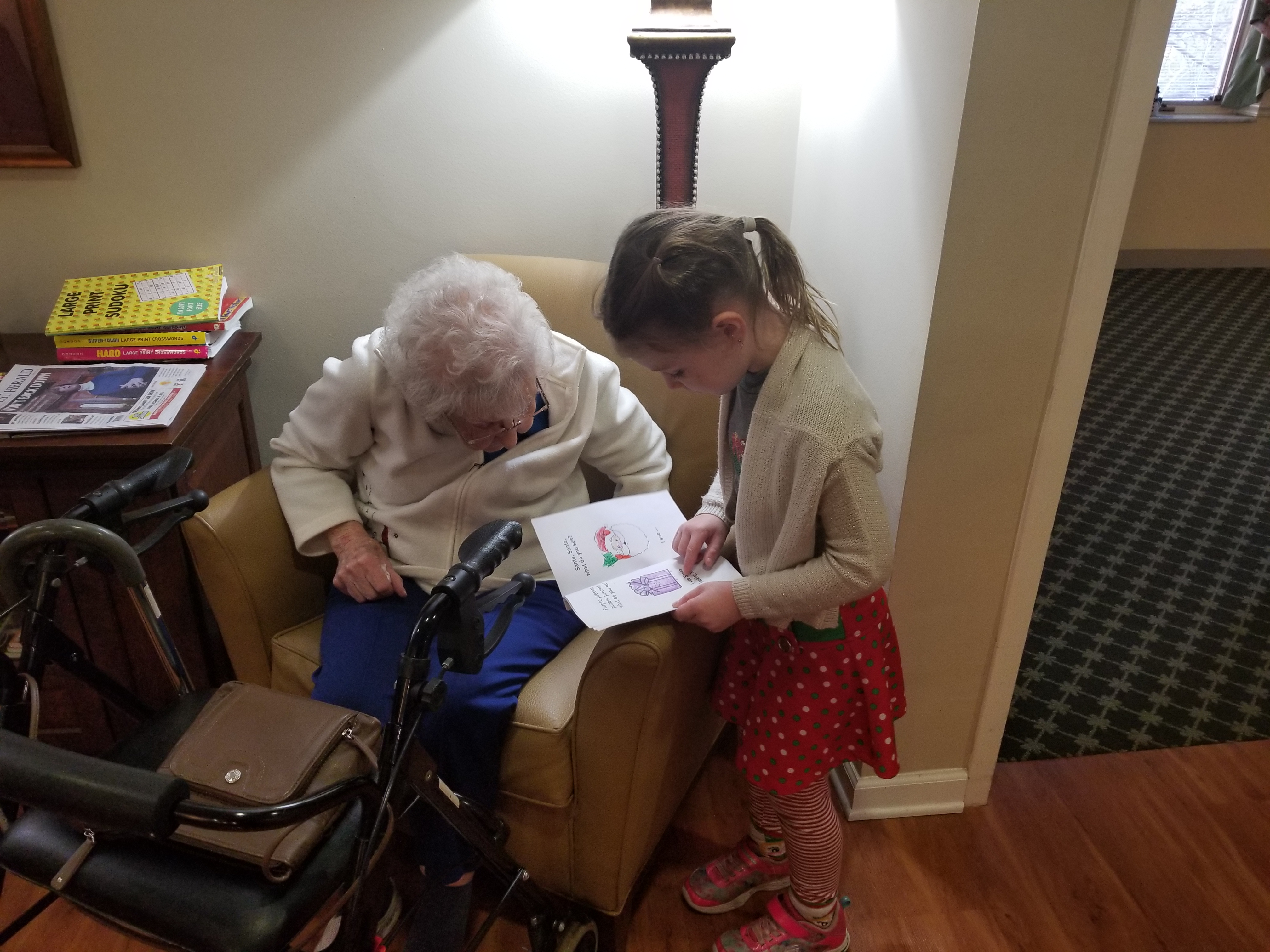 VDELC student reading with a Hearthstone Manor resident